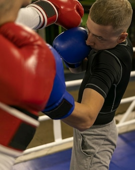 Male boxer practicing in the ring with trainer