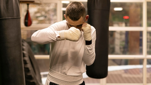 Male boxer practicing with punching bag