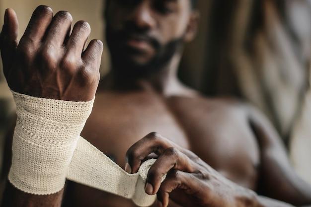 Боксер мужского пола, надевая ремень на руку