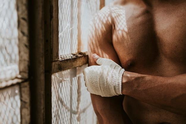 彼の手にストラップを置く男性ボクサー