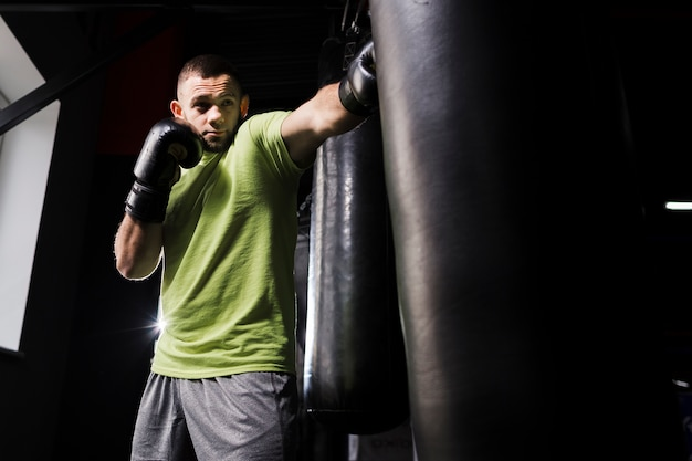 Male boxer in t-shirt practicing in protective gloves