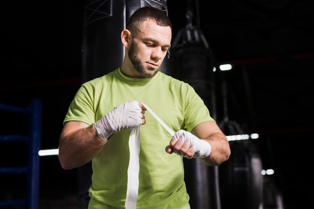 Male boxer in t-shirt putting on protection for hands