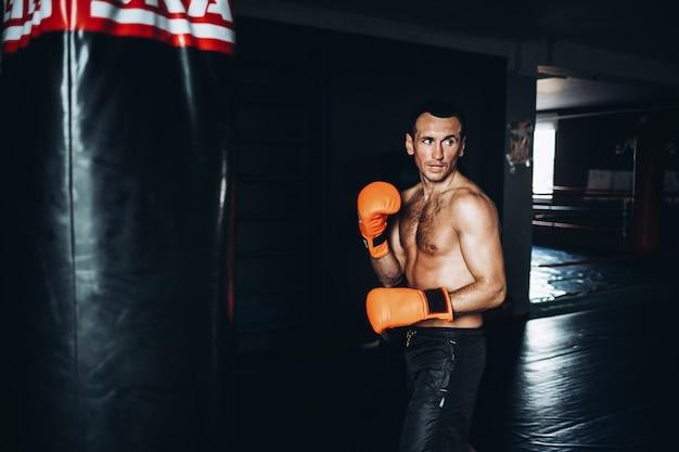 Male boxer training with punching bag in dark gym.