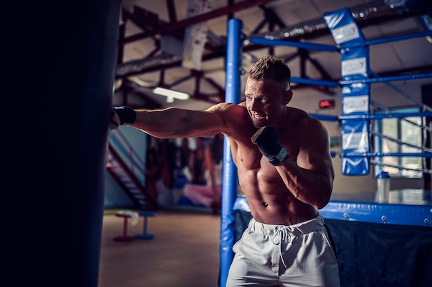Male boxer training with punching bag in dark sports hall. young boxer training on punching bag.
