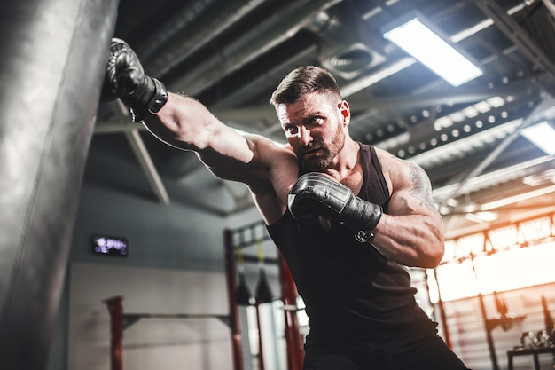 Male boxer training with punching bag in dark sports hall.