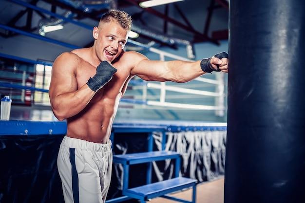 暗いスポーツホールでサンドバッグを使ってトレーニングする男性ボクサー。サンドバッグの若いボクサートレーニング。