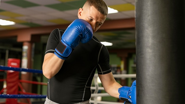 Male boxer with gloves training at the ring