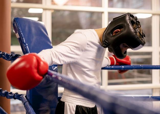 リングにヘルメットと手袋を持つ男性のボクサー