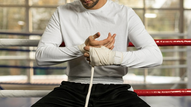 Male boxer wrapping his hands before training in the ring with cord