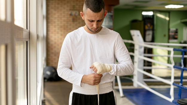 Male boxer wrapping his hands before training in the ring with ribbon