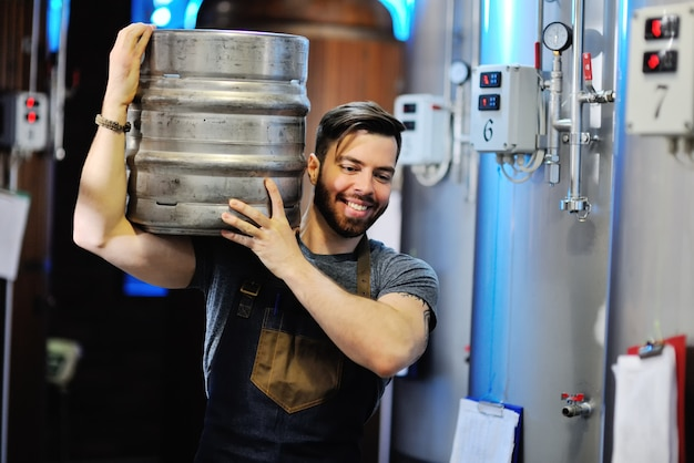 Male brewer with a metal beer barrel