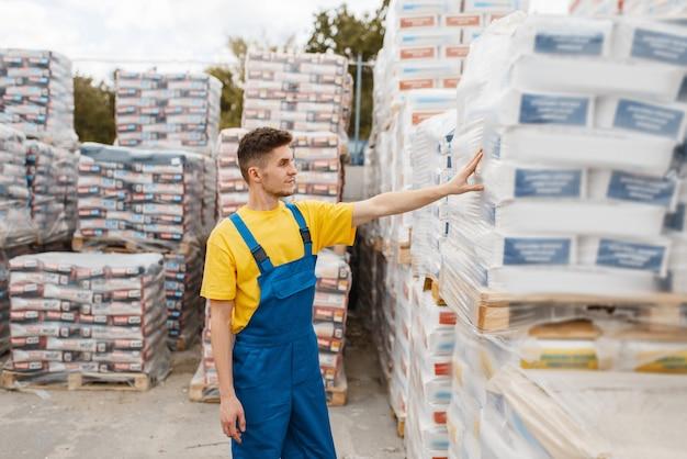 Мужчина-строитель у поддонов строительных материалов в строительном магазине. конструктор в униформе смотрит на товары в магазине своими руками