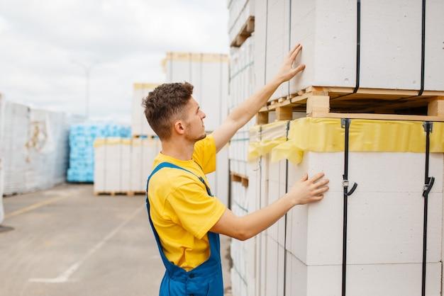 Строитель-мужчина у поддонов изоляционного материала в строительном магазине. конструктор в униформе осматривает товары в магазине своими руками