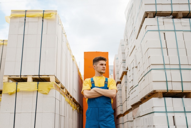 Male builder between big pallets of building materials in hardware store. constructor in uniform look at the goods in diy shop