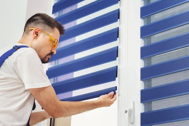 Плотник-строитель снимает синие жалюзи на окнах, ремонтирующих и проверяющих ткань Premium Фотографии