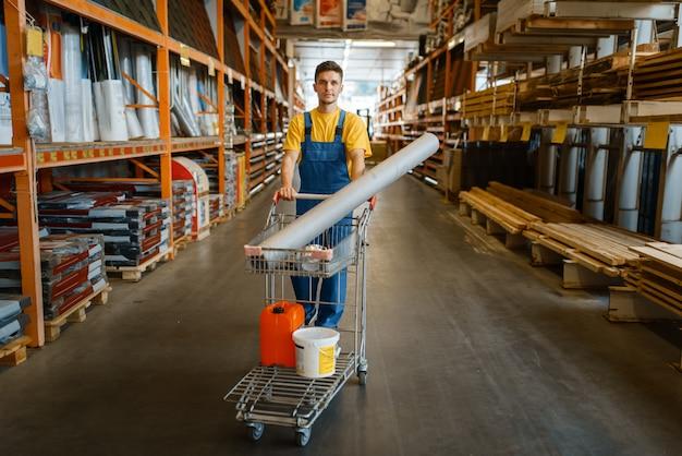 Строитель-мужчина несет строительные материалы в тележке