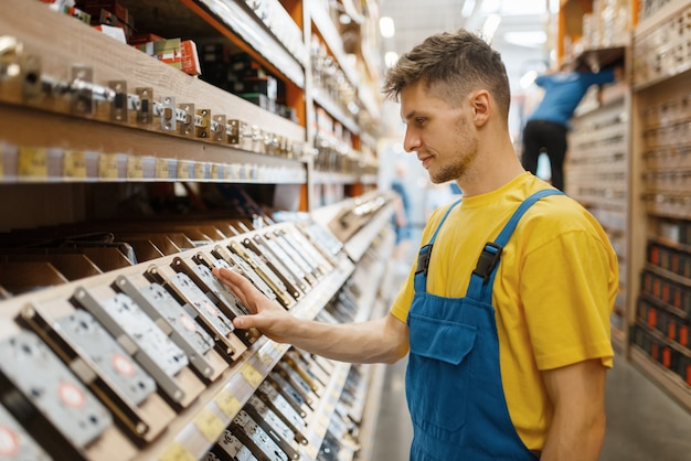 Male builder choosing door lock at the shelf in hardware store. constructor in uniform look at the goods in diy shop