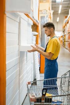 Строитель-мужчина выбирает изоляцию для стен в строительном магазине. покупатель смотрит на товары в магазине своими руками