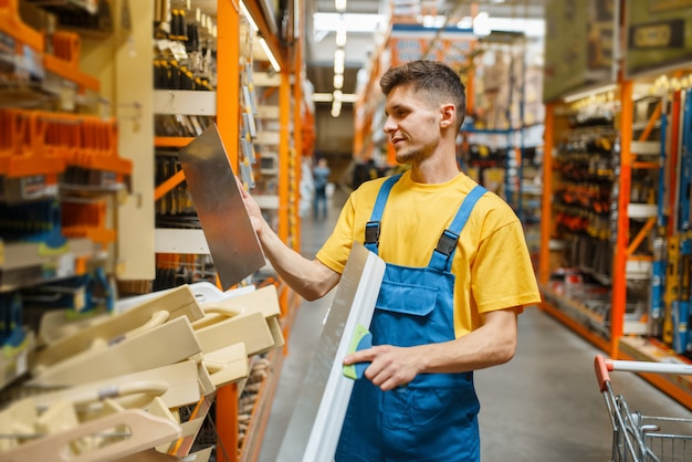 Строитель-мужчина, выбирая уровень стяжки в строительном магазине. конструктор в униформе смотрит на товары в магазине своими руками