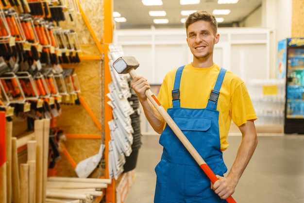 Male builder choosing sledgehammer at the shelf in hardware store. constructor in uniform look at the goods in diy shop