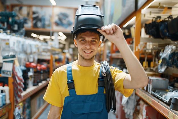 Male builder choosing welding helmet at the shelf in hardware store. constructor in uniform look at the goods in diy shop