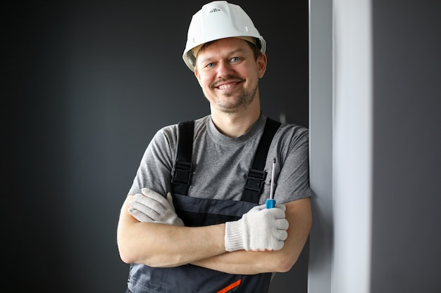 Male builder in coveralls and hard hat smiling