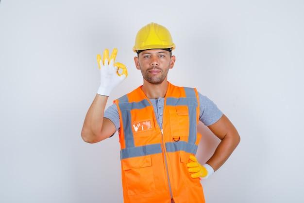 Строитель-мужчина делает хорошо жест рукой на талии в форме, шлеме, перчатках, вид спереди.