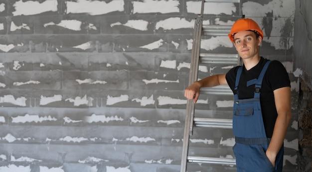 Строитель-мужчина, одетый в рабочую одежду и оранжевую каску. стоит у стены, прислонившись к лестнице. копировать пространство