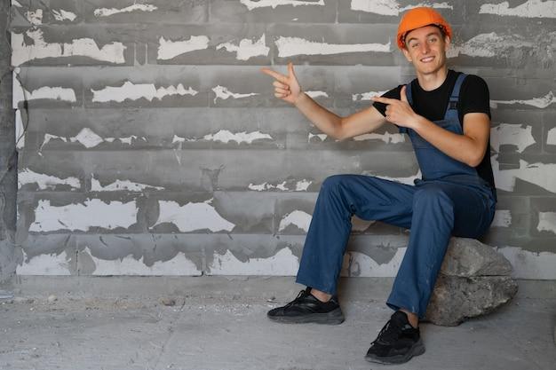 Строитель-мужчина, одетый в рабочую одежду и оранжевую маску. сядьте на камень, указательные пальцы на пустом месте для текста.
