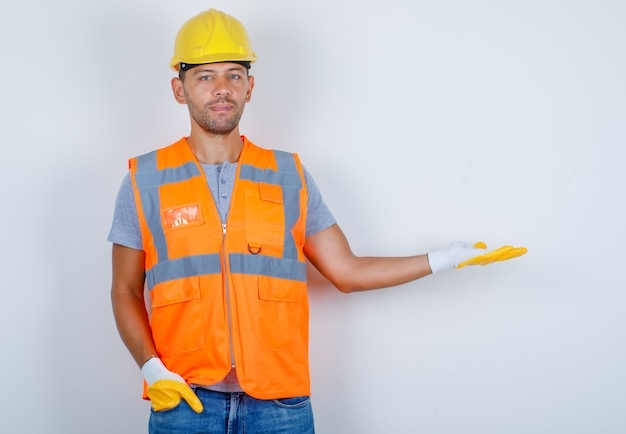 Male builder gesturing as welcoming with hand in pocket in uniform, jeans, helmet, gloves, front view.
