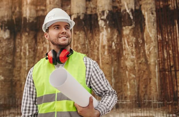 Мужчина-строитель держит план, стоя на строительной площадке
