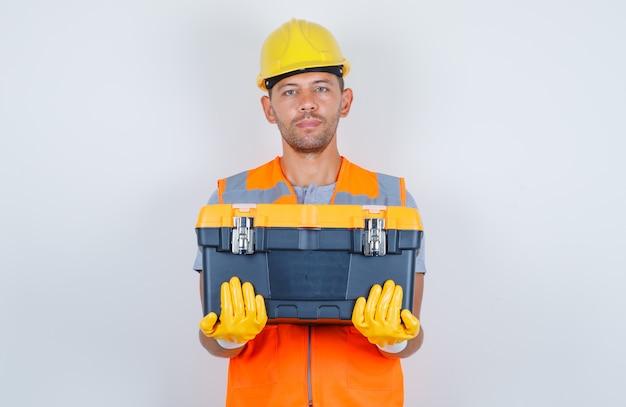 Строитель-мужчина держит пластиковый ящик для инструментов в форме, шлеме, перчатках, вид спереди.