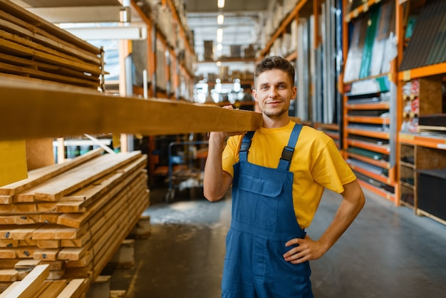 Male builder holds wooden boards in hardware store. customer look at the goods in diy shop