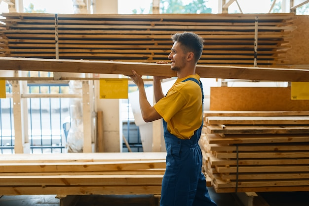 Male builder holds wooden boards in hardware store