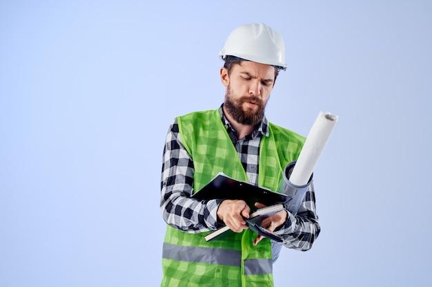 白いヘルメットの青写真の男性ビルダープロのスタジオ業界。高品質の写真