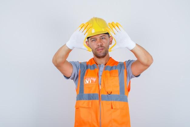 Строитель мужского пола в форме, шлеме, перчатках, показывающих рамку пальца, вид спереди.