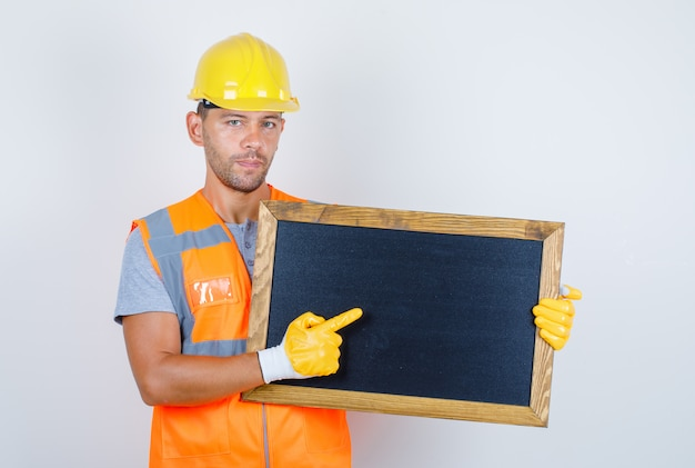 Строитель-мужчина в форме, шлеме, перчатках, показывая что-то на доске, вид спереди.