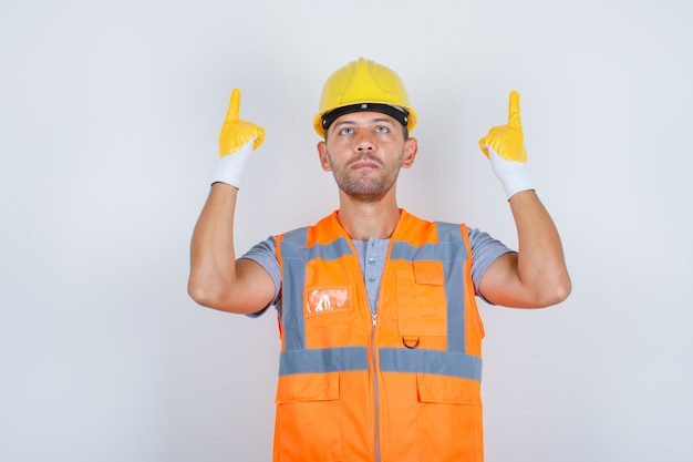 Male builder lifting his index fingers up in construction uniform front view.
