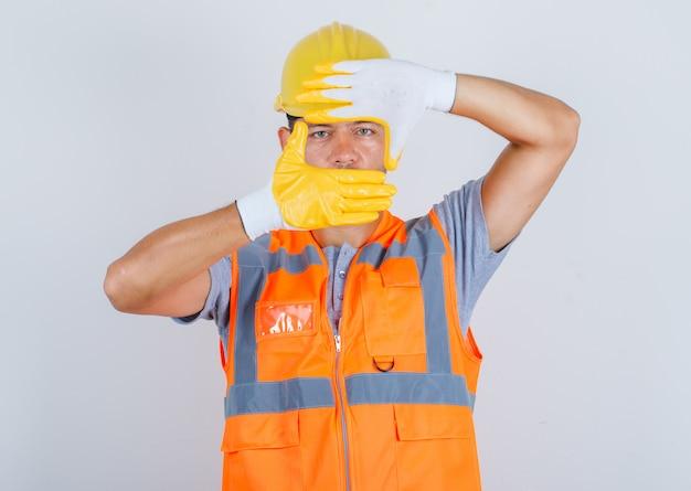 Мужчина-строитель смотрит через рамку, образованную руками в форме, вид спереди.