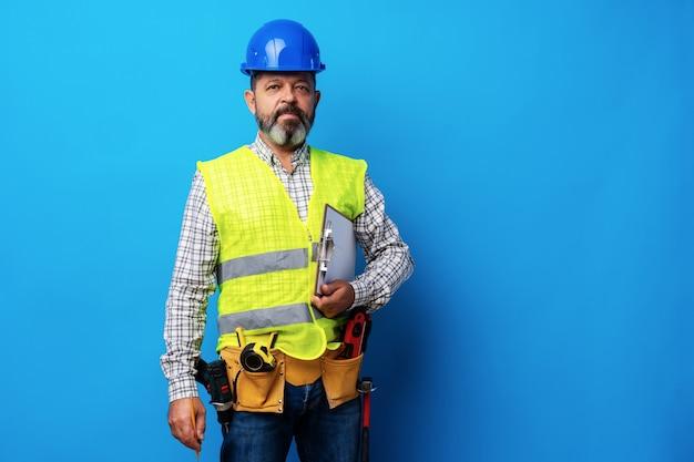 파란색 배경에 클립보드를 들고 제복을 입은 남성 빌더 또는 핸디