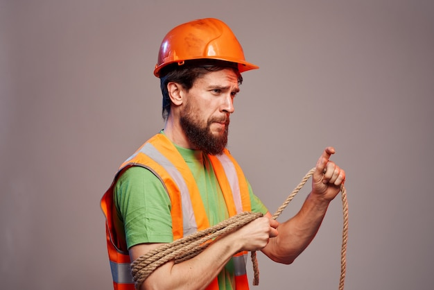 Male builder orange hard hat work professional gray background. high quality photo