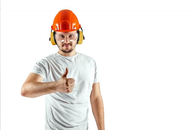 Male builder in orange helmet shows thumb up isolated on white background