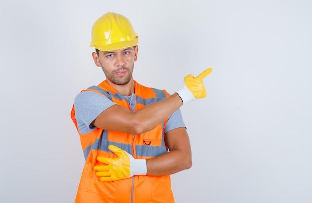 Мужской строитель, указывая пальцем в форме, шлеме, перчатках, вид спереди.