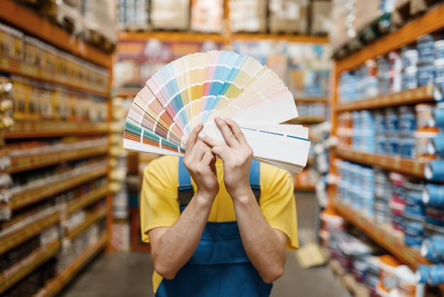 Male builder showing color palette in hardware store. constructor in uniform look at the goods in diy shop, paint department