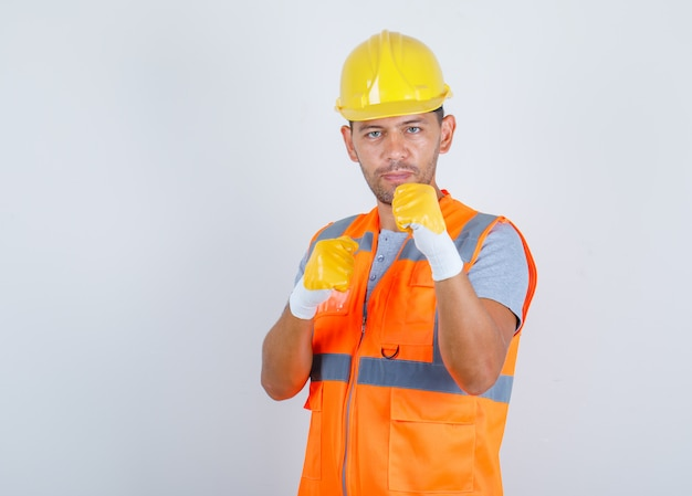 Male builder showing fists as boxer in uniform, helmet, gloves front view.