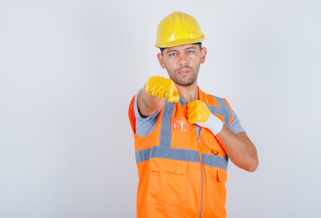 Male builder showing fists as boxer in uniform, helmet, gloves and looking serious, front view