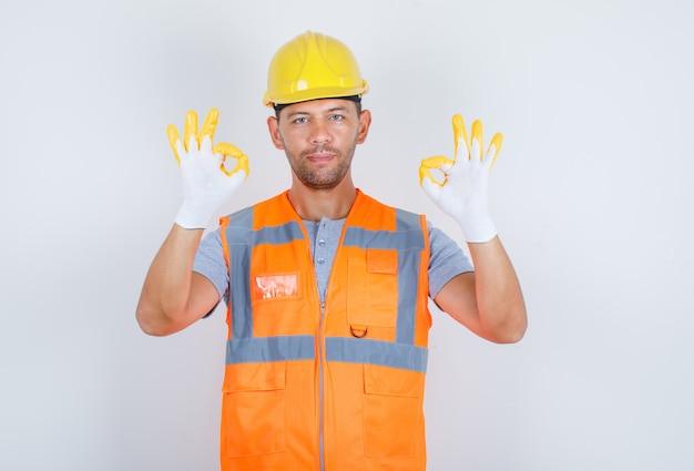 Строитель-мужчина показывает хорошо знаком с руками в униформе и выглядит уверенно, вид спереди.