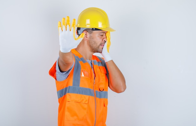 Male builder showing stop to camera in uniform, helmet, gloves, front view.