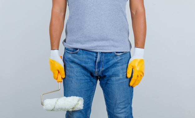 Male builder in t-shirt, jeans, gloves holding paint roller, front view.