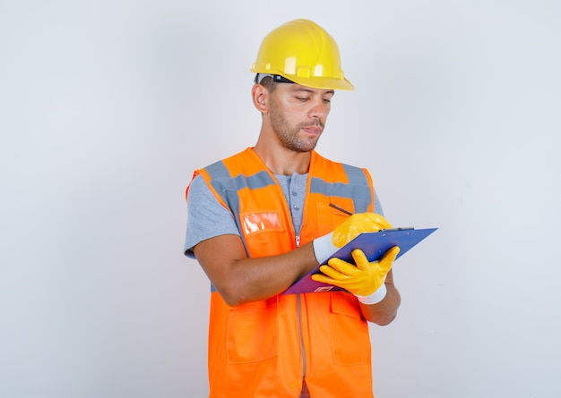 Male builder taking notes on clipboard in uniform, helmet, gloves and looking busy, front view